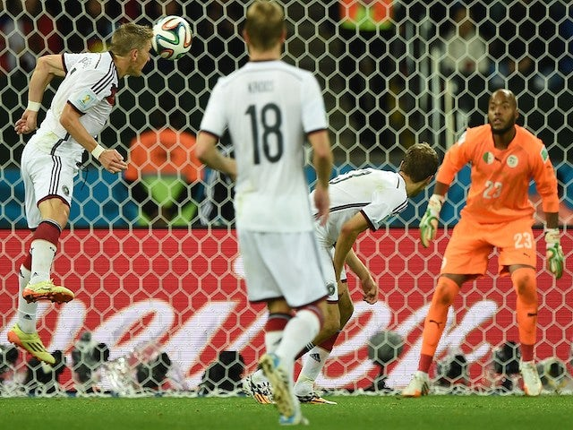 Germany's midfielder Bastian Schweinsteiger (L) heads the ball during a Round of 16 football match between Germany and Algeria on June 30, 2014