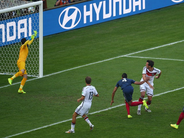 Mats Hummels of Germany scores his team's first goal on a header against Raphael Varane of France and past goalkeeper Hugo Lloris during the 2014 FIFA World Cup Brazil Quarter Final match between France and Germany at Maracana on July 4, 2014