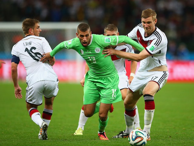 Islam Slimani of Algeria is challenged by Philipp Lahm (L) and Per Mertesacker of Germany during the 2014 FIFA World Cup on June 30, 2014