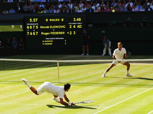 Novak Djokovic of Serbia dives to make a return as Roger Federer of Switzerland stands at the net during the Gentlemen's Singles Final match at Wimbledon on July 6, 2014