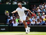 Roger Federer of Switzerland stretches to make a return during the Gentlemen's Singles Final match against Novak Djokovic on July 6, 2014