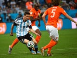 Netherlands' defender Bruno Martins Indi watches as Argentina's forward and captain Lionel Messi controls the ball past Netherlands' defender Daley Blind during the 2014 FIFA World Cup Brazil Semi Final match between the Netherlands and Argentina at Arena