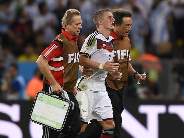 Germany's midfielder Bastian Schweinsteiger (C) is escorted off the pitch by medics after clashing with Argentina's forward Sergio Aguero (unseen)during the final football match on July 13, 2014