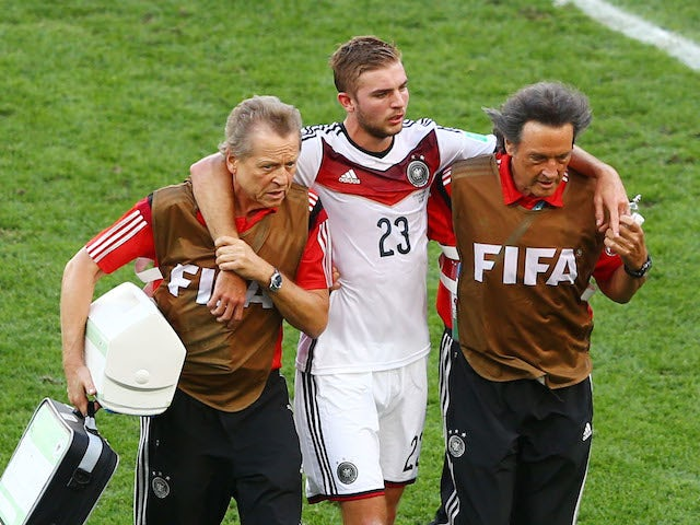 Christoph Kramer of Germany is helped off the field by trainers during the 2014 FIFA World Cup Brazil Final match between Germany and Argentina at Maracana on July 13, 2014