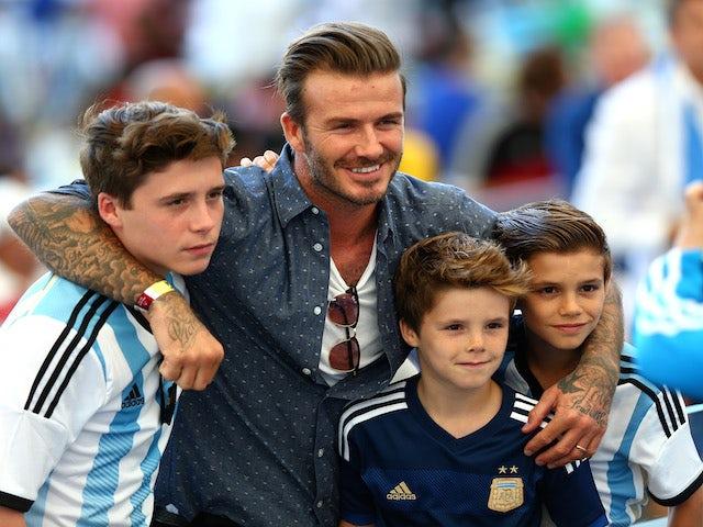 Former England international David Beckham and sons Brooklyn Beckham (L), Cruz Beckham (2nd R) and Romeo Beckham (R) prior to the 2014 FIFA World Cup final on July 13, 2014