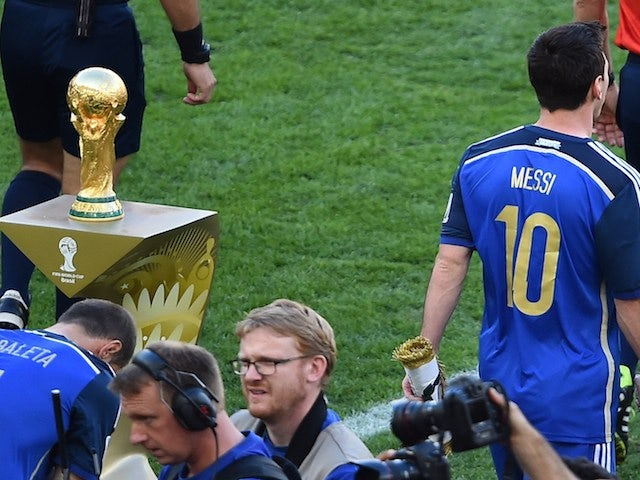 Argentina's forward and captain Lionel Messi (R) walks past the World Cup ahead of the final football match between Germany and Argentina on July 13, 2014