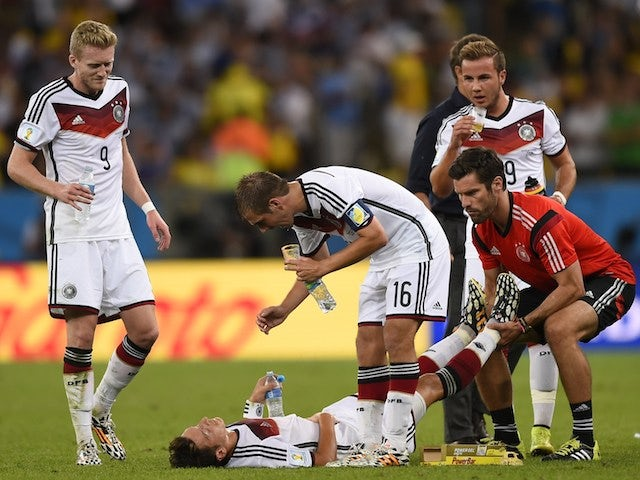 Germany's forward Andre Schuerrle (L) and Germany's defender and captain Philipp Lahm (C) speak with Germany's midfielder Mesut Ozil (bottom) as hereceives medical treatment on July 13, 2014
