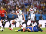 Germany's forward Miroslav Klose (2R) is fouled by Argentina's midfielder Javier Mascherano, resulting in a yellow card, during the second half of the 2014 FIFA World Cup final  on July 13, 2014