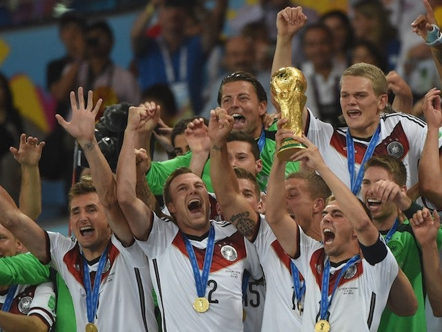 Germany's defender and captain Philipp Lahm (front-R) holds up the World Cup trophy as he celebrates with his teammates after winning the 2014 FIFA World Cup final football match on July 13, 2014