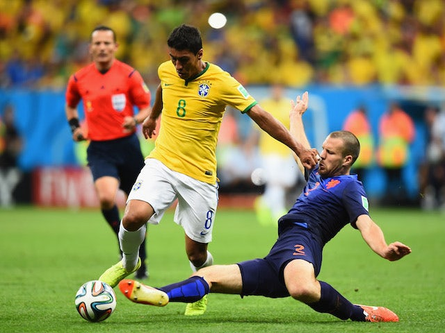 Ron Vlaar of the Netherlands challenges Paulinho of Brazil during the 2014 FIFA World Cup Brazil Third Place Playoff match on July 12, 2014
