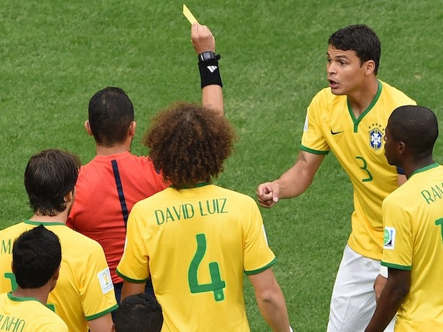 Algerian referee Djamel Haimoudi (L) gives Brazil's defender and captain Thiago Silva a yellow card after he commited a foul on Netherlands' forward Arjen Robben on July 12, 2014