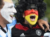 An Argentina and Germany fan with their faces painted in the national colors cheer prior to the 2014 FIFA World Cup final football match between Germany and Argentina at the Maracana Stadium in Rio de Janeiro on July 13, 2014