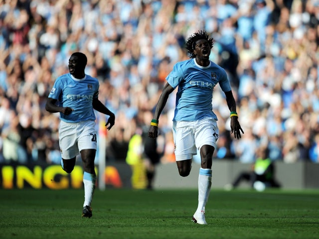 Emmanuel Adebayor of Manchester City runs towards the Arsenal fans as he celebrates scoring with team-mate Kolo Toure during the Barclays Premier League match between Manchester City and Arsenal at the City of Manchester Stadium on September 12, 2009