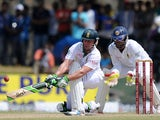 South Africa cricketer AB de Villiers is watched by Sri Lankan wicketkeeper Dinesh Chandimal as he plays a shot during the fourth day of the opening Test match between Sri Lanka and South Africa at the Galle International Cricket Stadium in Galle on July