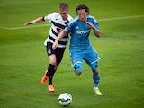 Billy Jones of Sunderland is challenged by Adam Mitchell of Darlington during a pre-season friendly match between Darlington and Sunderland at Heritage Park on July 19, 2014