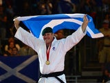 Scotland's gold medalist Christopher Sherrington poses with the Scottish flag at the medal ceremony for the men's judo +100kg class at the SECC Precinct during the 2014 Commonwealth Games in Glasgow, Scotland on July 26, 2014