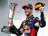 Daniel Ricciardo of Australia and Infiniti Red Bull Racing celebrates victory with the trophy on the podium after the Hungarian Formula One Grand Prix at Hungaroring on July 27, 2014