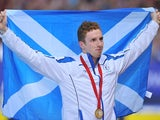 Daniel Wallace holds the Scottish flag proudly after taking gold in the 400m individual medley on July 25, 2014