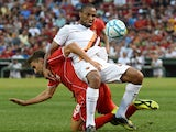 Liverpool's Fabio Borini tussles with Roma's Seydou Keita during a friendly soccer match between Liverpool and Roma at Fenway Park, July 23, 2014