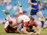 Matthew Russell of Warrington Wolves is tackled by Jonny Lomax and Joe Greenwood of St Helens during the Super League match between Warrington Wolves and St Helens at Etihad Stadium on May 18, 2014