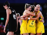 Anna Harrison of New Zealand walks off as Laura Geitz, Kimberley Ravaillion and Renae Hallinan of Australia celebrate winning the gold medal match between Australia and New Zealand at SECC Precinct during day eleven of the Glasgow 2014 Commonwealth Games