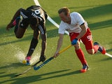 Shaquille Daniel of Trinidad and Tobago and Barry Middleton of England compete for the ball during the Men's preliminary match between England and Trinidad and Tobago at Glasgow National Hockey Centre during day one of the Glasgow 2014 Commonwealth Games