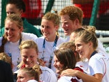 Prince Harry poses for a photograph with the England women's hockey team on July 28, 2014