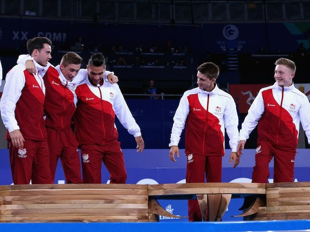 Gymnast Sam Oldham is helped onto the top of the podium by England teammates Kristian Thomas and Louis Smith, with Max Whitlock and Nile Wilson watching on, after they won team gold in the Commonwealth Games on July 29, 2014