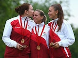Sian Gordon, Ellen Falkner and Sophie Tolchard of England sing the nation anthem as they celebrate victory in the women's triples final match between England and Australia at Kelvingrove Lawn Bowls Centre during day eight of the Glasgow 2014 Commonwealth