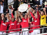 Manchester United's Serbian player Nemanja Vidic lifts the trophy after winning the match against Manchester City 3-2 during the FA Community Shield football match at Wembley Stadium in London, England on August 7, 2011