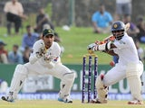 Sri Lankan cricketer Kaushal Silva is watched by Pakistan wicketkeeper Sarfraz Ahmed as he plays a shot during the second day of the opening Test match between Sri Lanka and Pakistan at the Galle International Cricket Stadium in Galle on August 7, 2014