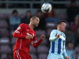 Matthew Connolly of Cardiff City outjumps Danny Swanson of Coventry City to head the ball during the Capital One Cup First Round match between Covenrty City and Cardiff City at Sixfields Stadium on August 13, 2014
