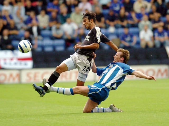 Chelsea's Paulo Ferreira is tackled by Wigan's Alan Mahon during today's premiership clash at the JJB Stadium, in Wigan 14 August 200