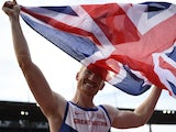 Great Britain's Greg Rutherford, holding his national flag, celebrates after winning the Men's Long Jump final during the European Athletics Championships at the Letzigrund stadium in Zurich on August 17, 2014