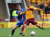 Liam Polworth of Inverness vies with Keith Lasley of Motherwell during the Scottish Premiership League Match between Motherwell and Inverness Caledonian Thistle at Fir Park on August 16, 2014