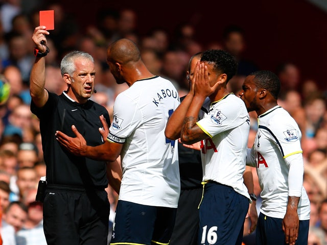 Kyle Naughton of Spurs reacts after receiving a red card for handball as Younes Kaboul of Spurs remenstrates with referee Chris Foy during the Barclays Premier League match between West Ham United and Tottenham Hotspur at Boleyn Ground on August 16, 2014