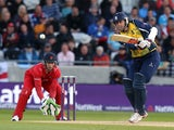 Rikki Clarke of Birmingham Bears drives at the ball with Jos Buttler of Lancashire Lightning looking on during the Natwest T20 Blast Final match between Birmingham Bears and Lancashire Lightning at Edgbaston on August 23, 2014