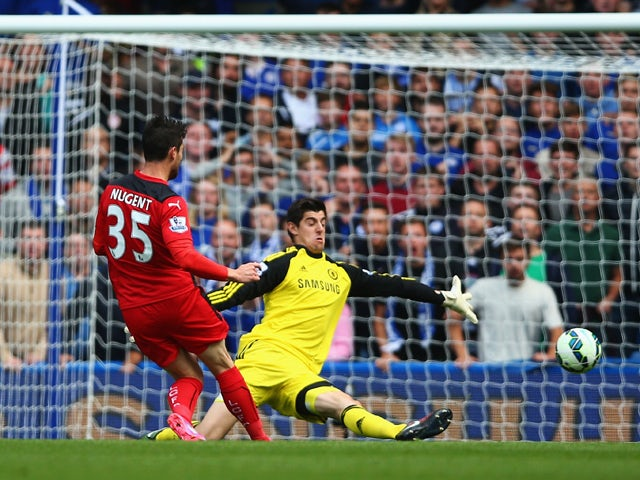 Thibaut Courtois of Chelsea saves from David Nugent of Leicester City during the Barclays Premier League match between Chelsea and Leicester City at Stamford Bridge on August 23, 2014