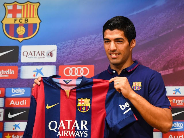 Luis Suarez poses for the media during a press conference as part of his presentation as a new FC Barcelona player at Camp Nou on August 19, 2014