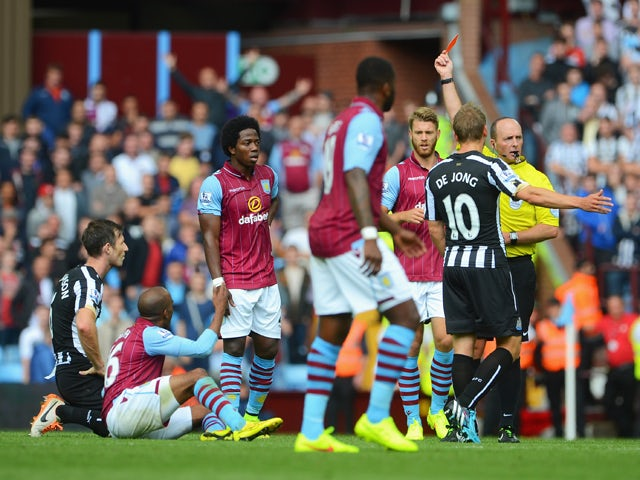Referee Mike Dean shows the red card to Mike Williamson of Newcastle United during the Barclays Premier League match between Aston Villa and Newcastle United at Villa Park on August 23, 2014