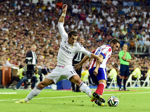 Real Madrid's Welsh forward Gareth Bale vies with Atletico Madrid's midfielder Koke during the Spanish Supercup first-leg football match Real Madrid CF vs Club Atletico de Madrid at the Santiago Bernabeu stadium in Madrid on August 19, 2014