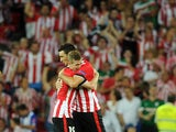 Athletic Bilbao's forward Aritz Aduriz celebrates with his teammate forward Iker Muniain (L) after scoring during the UEFA Champions League play-off second leg football match Athletic Bilbao vs SSC Napoli at the San Mames stadium in Bilbao on August 27, 2