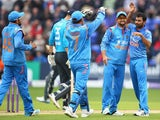 Mohammed Shami of India celebrates with Suresh Raina and MS Dhoni after capturing the wicket of Alastair Cook of England during the second Royal London One-Day Series match between England and India at the SWALEC Stadium on August 27, 2014