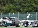 Mercedes-AMG's British driver Lewis Hamilton (L) and and Mercedes-AMG's German driver Nico Rosberg collide at the Spa-Francorchamps ciruit in Spa on August 24, 2014