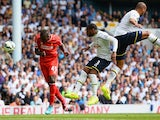 Mario Balotelli of Liverpool heads the ball under pressure from Danny Rose and Younes Kaboul of Spurs during the Barclays Premier League match on August 31, 2014