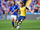 Arsenal's German midfielder Mesut Ozil (R) runs with the ball chased by Leicester City's Algerian midfielder Riyad Mahrez (L) during the English Premier League football match on August 31, 2014