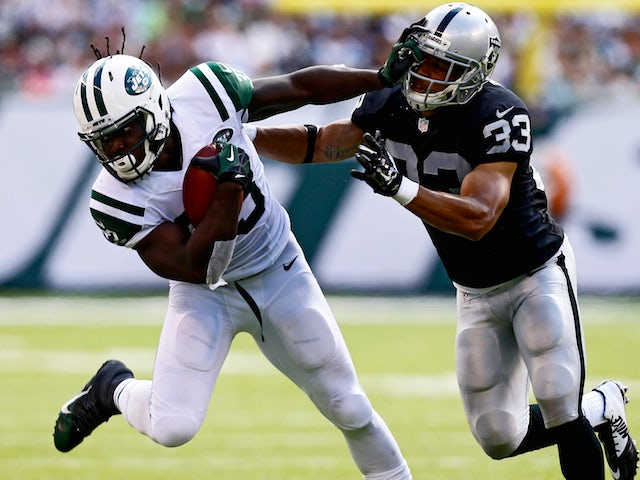 Chris Ivory #33 of the New York Jets stiffarms Tyvon Branch #33 of the Oakland Raiders during the second quarter at MetLife Stadium on September 7, 2014