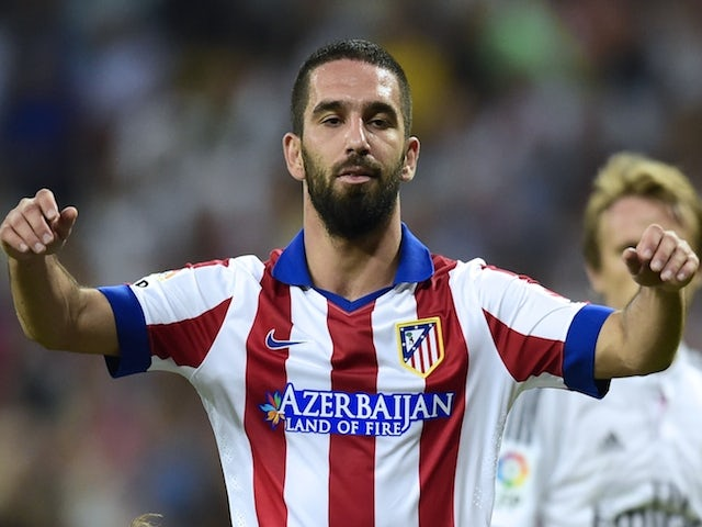 Atletico Madrid's Turkish midfielder Arda Turan (top) celebrates with Atletico Madrid's French forward Antoine Griezmann after scoring during the Spanish league football match against Real Madrid on September 13, 2014