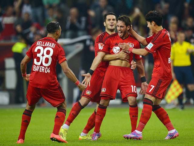 Leverkusen's midfielder Hakan Calhanoglu celebrates scoring the 2-2 goal with his teammates during the German first division Bundesliga football match Bayer 04 Leverkusen vs SV Werder Bremen, in Leverkusen, western Germany on September 12, 2014