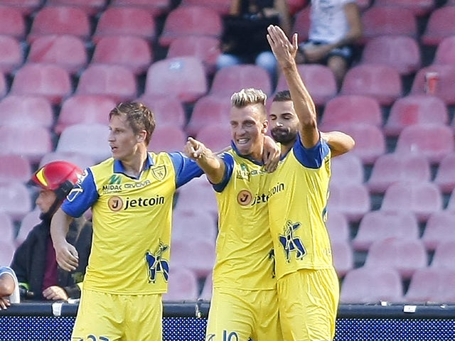 Chievo's Argentinian forward Maxi Lopez celebrates with teammates after scoring during the Italian Serie A football match SSC Napoli vs AC Chievo Verona in San Paolo Stadium on September 14, 2014
